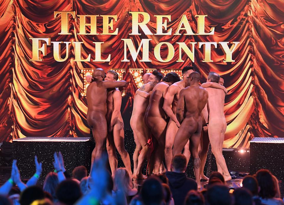 The blokes strip off for the cameras in the name of cancer awareness. (REX)