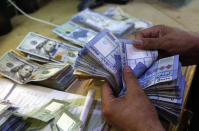 FILE - In this August 20, 2018 file photo, a man counts Lebanese pounds at an exchange shop, in Beirut, Lebanon. The Lebanese pound has hit a record low against the dollar on the black market as the country's political crisis deepens and foreign currency reserves dwindle further. The dollar was trading at 9,975 Lebanese pounds on Tuesday. (AP Photo/Hussein Malla, File)