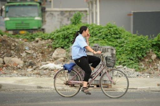 A woman on a bicycle covers her nose against the stench rising from a garbage dump in Songjiang district. Residents claim the incinerator could affect the health of hundreds of thousands of people and call for moving the landfill, which towers up to 17 metres and covers an area the size of a football field