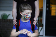 Rachel Adamus holds her son Paul, 7, on their porch before the bus arrives for the first day of school on Monday, Aug. 3, 2020, in Dallas, Ga. Adamus is among tens of thousands of students in Georgia and across the nation who were set to resume in-person school Monday for the first time since March. (AP Photo/Brynn Anderson)