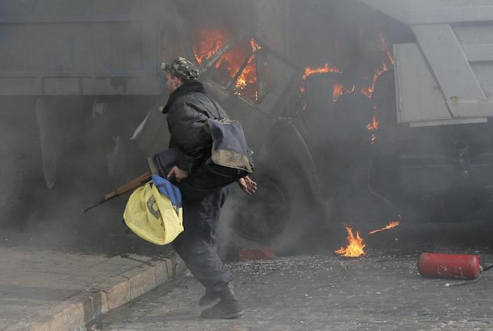 In this Friday, Feb. 21, 2014 file photo, a man with a gun runs along a street during a clash between opposition protesters and riot police at a burning barricades near the Presidential office in Kiev, Ukraine. As questions circulate about who was behind the lethal snipers that sowed death and terror in Ukraine's capital, doctors and others told the AP the similarity of bullets wounds suffered by opposition victims and police indicates the snipers were specifically trying to stoke tensions and spark a larger, angrier clash between opposition fighters and government security forces.(AP Photo/Efrem Lukatsky, file)