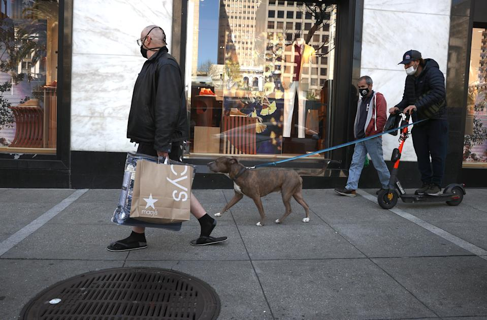SAN FRANCISCO, CALIFORNIA - APRIL 15: A pedestrian carries a shopping bag as he walks through the Union Square shopping district on April 15, 2021 in San Francisco, California. According to a report by the U.S. Commerce Department, retail sales surged 9.8 percent in March as Americans started to spend $1,400 government stimulus checks. (Photo by Justin Sullivan/Getty Images)