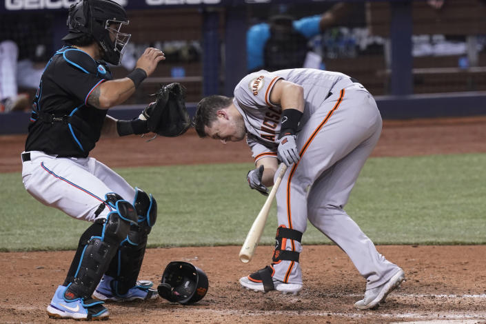 San Francisco Giants' Buster Posey reacts after being hit by a pitch from Miami Marlins' Sandy Alcantara during the seventh inning of a baseball game Saturday, April 17, 2021, in Miami. To the left is Marlins catcher Jorge Alfaro. (AP Photo/Marta Lavandier)