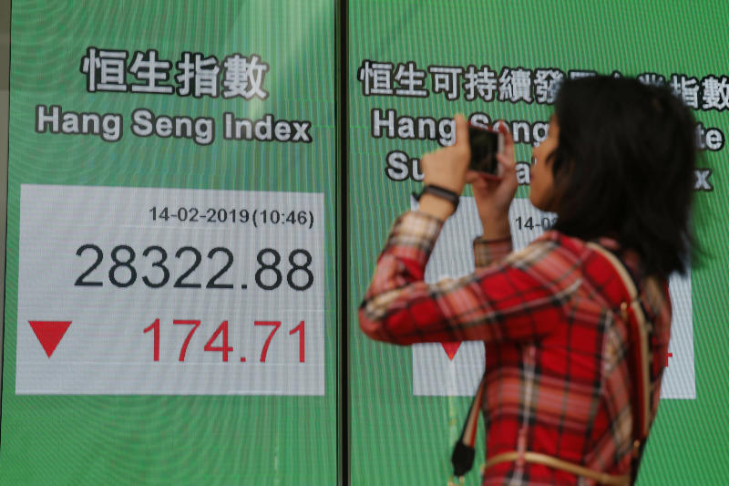 A woman takes a photograph in front of an electronic board showing Hong Kong share index outside a bank in Hong Kong, Thursday, Feb. 14, 2019. (AP Photo/Kin Cheung)