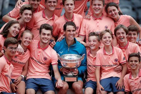 Tennis - French Open - Roland Garros, Paris, France - June 10, 2018 Spain's Rafael Nadal celebrates with ball boys, ball girls and the trophy after winning the final against Austria's Dominic Thiem REUTERS/Benoit Tessier