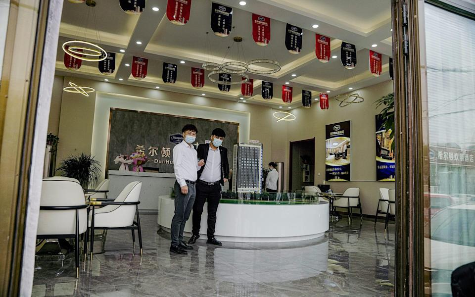 Two young men stand in a showroom for a new Hampton hotel complex