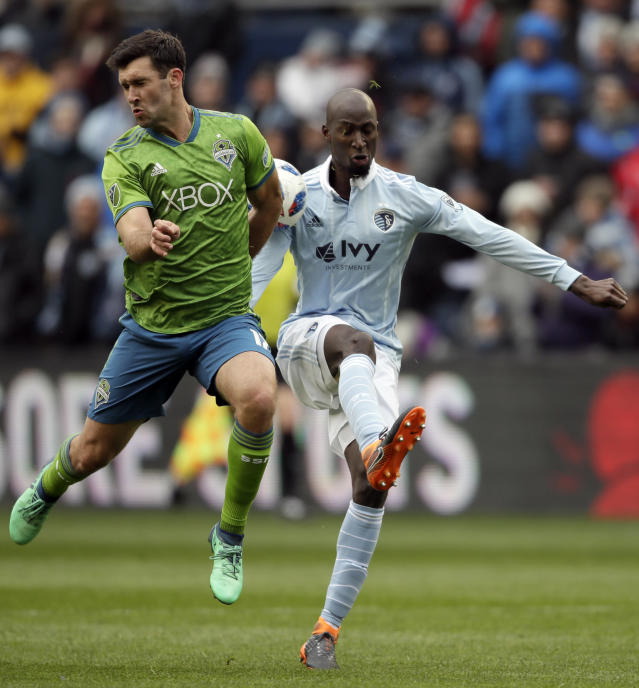 Seattle Sounders defender Will Bruin, left, blocks a kick by Sporting Kansas City defender Ike Opara, right, during the first half of an MLS soccer match in Kansas City, Kan., Sunday, April 15, 2018. (AP Photo/Orlin Wagner)