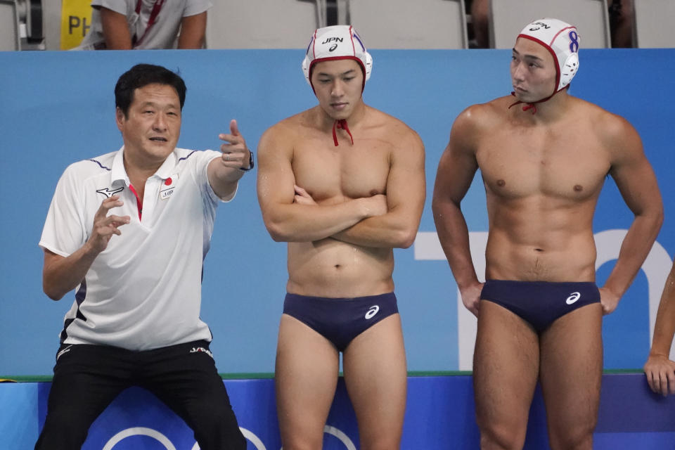 Japan's head coach Yoji Omoto talks with his players during a preliminary round men's water polo match against Hungary at the 2020 Summer Olympics, Tuesday, July 27, 2021, in Tokyo, Japan. (AP Photo/Mark Humphrey)