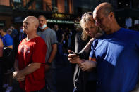 A couple gathers with others outside the National September 11 Memorial and Museum as they view on their smartphone a ceremony marking the 20th anniversary of the 9/11 terrorist attacks, Saturday, Sept. 11, 2021, in New York. (AP Photo/Matt Rourke)