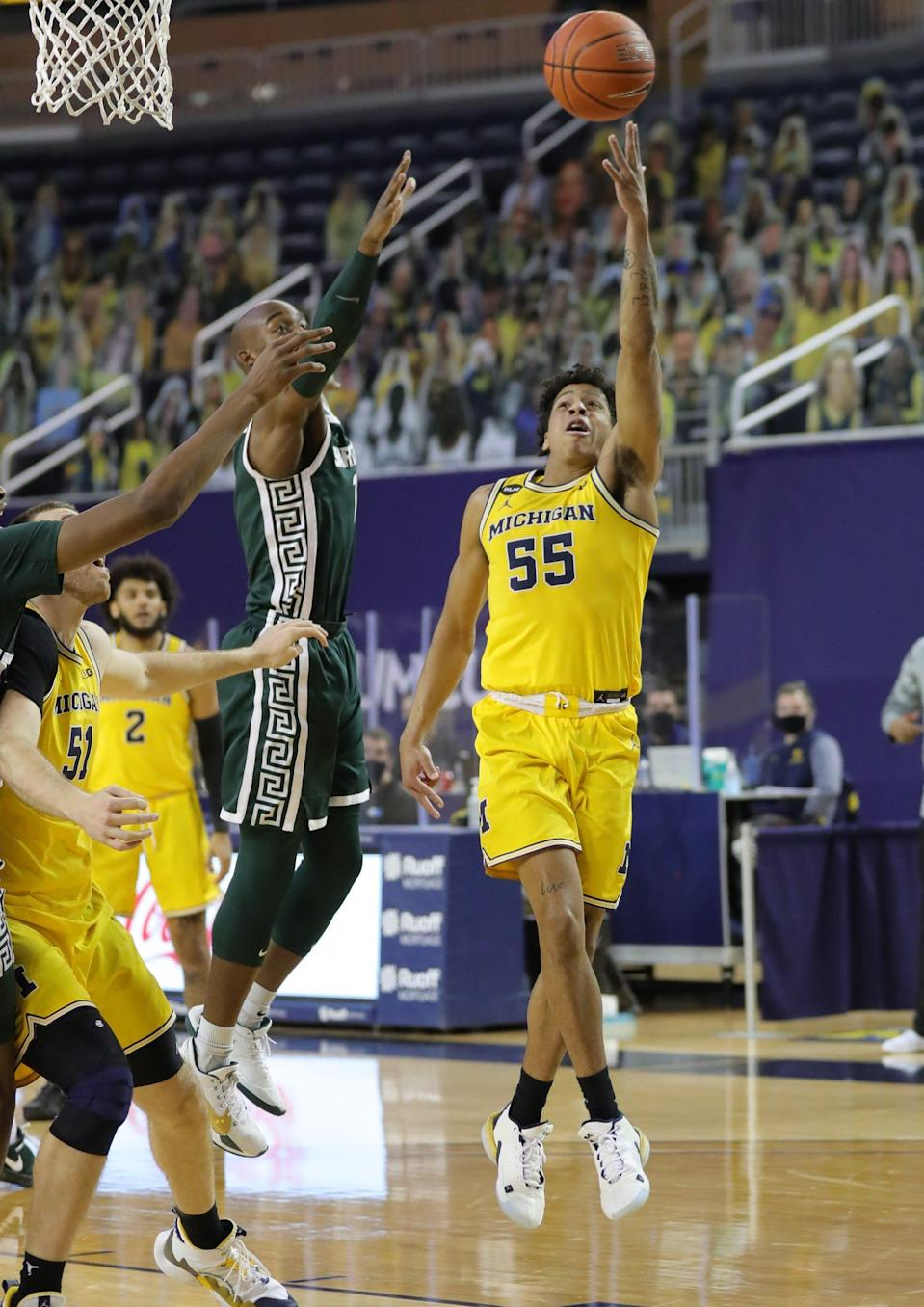 Michigan Wolverines guard Eli Brooks scores against Michigan State Spartans guard Joshua Langford on Thursday, March 4, 2021 at Crisler Center in Ann Arbor.
