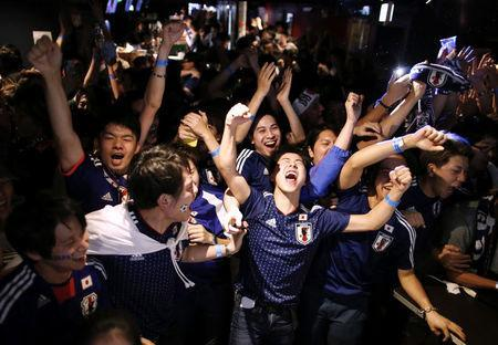 Japanese fans react after Japan's second goal against Senegal as they watch a broadcast of the World Cup Group H soccer match Japan vs Senegal, at a sports bar in Tokyo, Japan June 25, 2018. REUTERS/Issei Kato