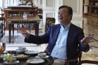 In this Aug. 20, 2019, photo, Huawei's founder Ren Zhengfei gestures as he chats with Huawei executives at the company campus in Shenzhen in Southern China's Guangdong province. Ren says its troubles with President Donald Trump are hardly the biggest crisis he has faced while working his way from rural poverty to the helm of China's first global tech brand. (AP Photo/Ng Han Guan)