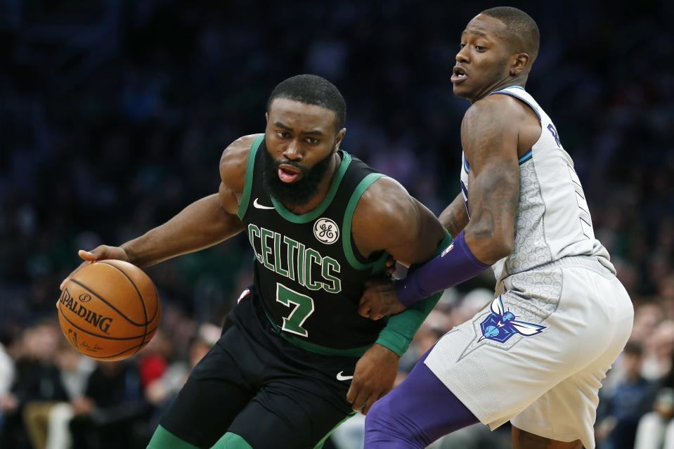 Boston Celtics' Jaylen Brown (7) drives past Charlotte Hornets' Terry Rozier, right, during the first half of an NBA basketball game in Boston, Sunday, Dec. 22, 2019. (AP Photo/Michael Dwyer)