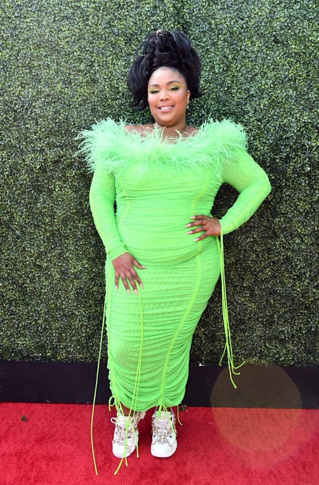 <p>The confidence it takes to rock a neon green dress will clue everyone in right away that you're dressed as Lizzo. Make sure you match your eye shadow to the dress, too. </p> <p><strong>What to wear:</strong> The brightest green dress you can find, a matching boa (to mimic the neckline), white sneakers, and a high ponytail.   </p>