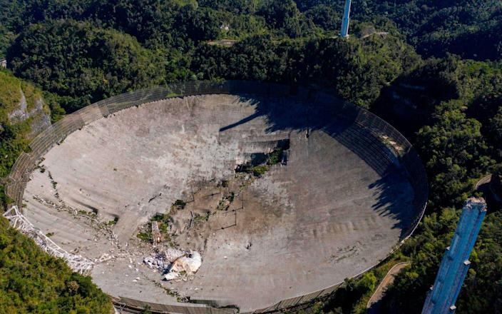 This aerial view shows the damage at the Arecibo Observatory after one of the main cables holding the receiver broke in Arecibo, Puerto Rico - AFP
