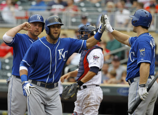 Kansas City Royals' Alex Gordon, front center, is congratulated by Billy Butler, left, and Josh Willingham, right, after his two-run home run off Minnesota Twins relief pitcher Caleb Thielbar during the fifth inning of a baseball game in Minneapolis, Sunday, Aug. 17, 2014. The Royals won 12-6. (AP Photo/Ann Heisenfelt)