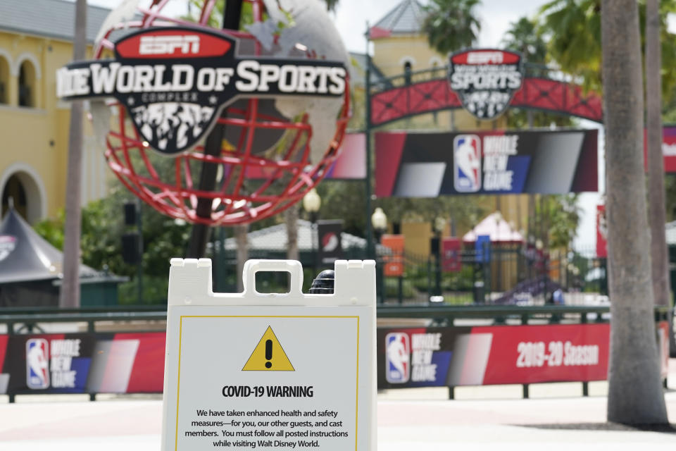 COVID-19 sign in front of ESPN's Wide World of Sports sign.