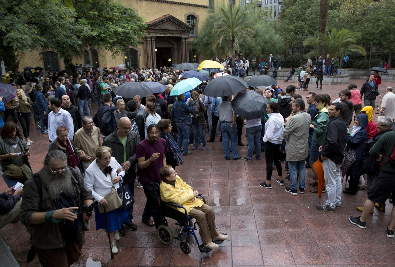 <p>Voters leave after casting their ballots as others wait in line at the Escola Industrial, a school assigned to be a polling station by the Catalan government in Barcelona. (AP) </p>