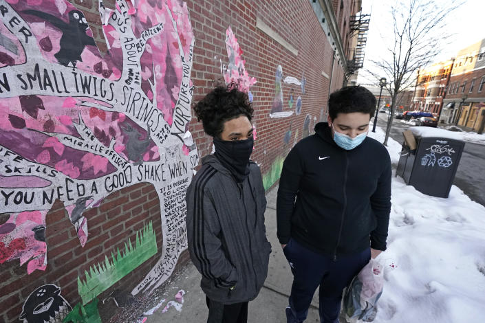 """High school sophomores Jose Cruz, left, and Mannix Resto, both of Chelsea, Mass., speak about the COVID-19 pandemic and how it has impacted them on Feb. 10, 2021. Resto fears the state's slow rollout of the vaccine will continue to prevent students from attending classes in-person. The 15-year-old says no one in his family has been vaccinated yet. """"I just want to know how much longer it's going to last,"""" Resto said. (AP Photo/Elise Amendola)"""