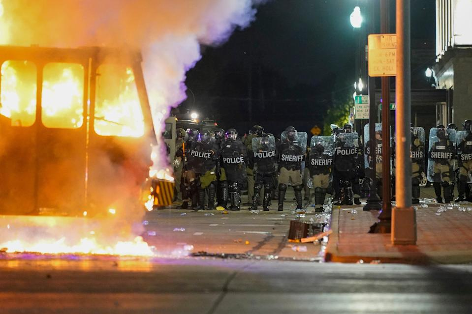 police line up behind a riot fire in kenosha