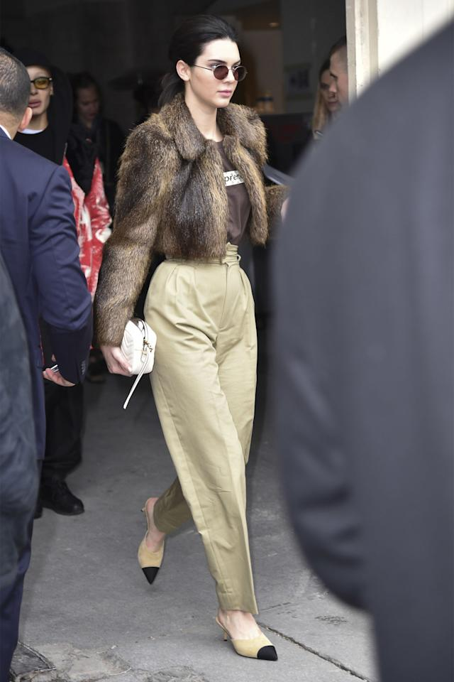 <p>In a browncropped fur coat, Supreme x Louis Vuitton t-shirt and high-waisted khaki pants with Chanel pumps and Krewe sunglasses while leaving the Chanel show in Paris.</p>