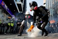 FILE PHOTO: An anti-government protester holds a tear gas canister during a protest in Hong Kong
