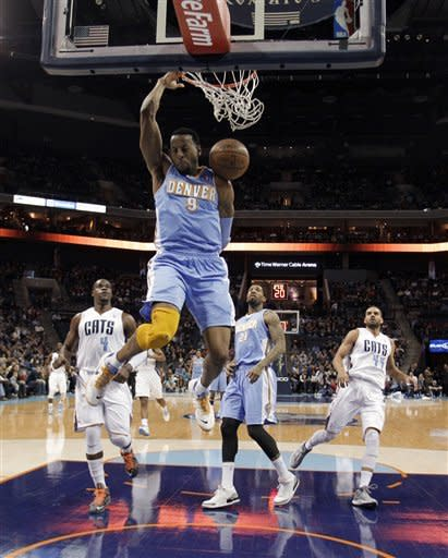 Denver Nuggets' Andre Iguodala (9) dunks as he gets in front of Charlotte Bobcats' Jeff Adrien (4), Nuggets' Wilson Chandler (21) and Bobcats' Jeffery Taylor (44) during the first half of an NBA basketball game in Charlotte, N.C., Saturday, Feb. 23, 2013. (AP Photo/Bob Leverone)