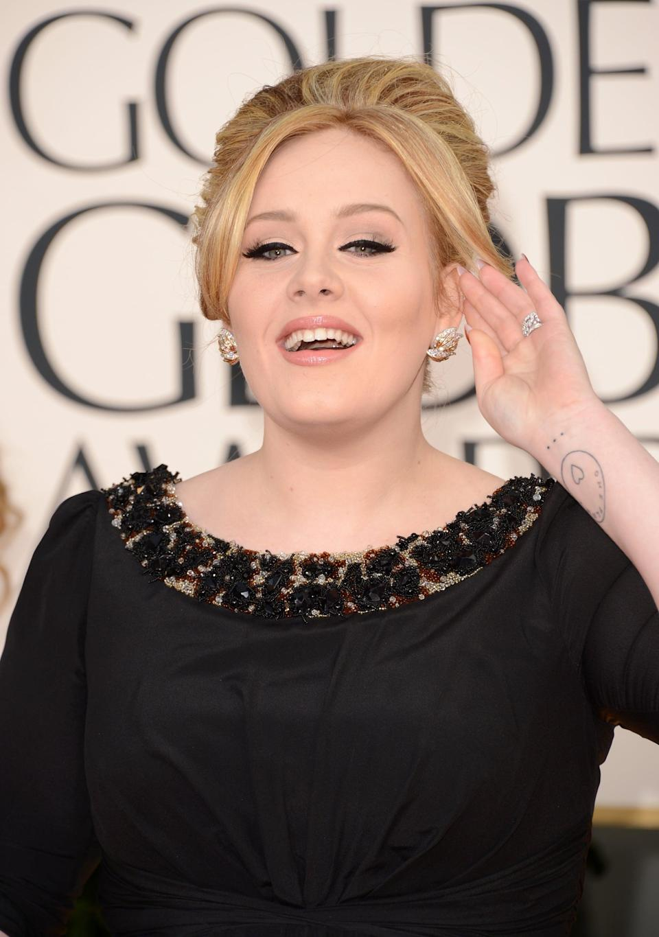 """<p>On her right wrist, the singer has a tattoo of a coin that reads """"One Penny,"""" honor of her mother whose name is Penny Adkins. Below the coin is an ellipsis which, according to <a href=""""https://bodyartguru.com/adele-tattoos/"""" class=""""link rapid-noclick-resp"""" rel=""""nofollow noopener"""" target=""""_blank"""" data-ylk=""""slk:Body Art Guru"""">Body Art Guru</a>, she got to match Civil Wars singer Joy Williams.</p>"""
