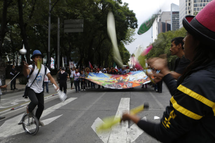 Jugglers join a protest by residents who live in Atenco who are against the construction of a new airport near their community, in Mexico City, Thursday, Aug. 23, 2018. Demonstrators marched through Mexico City Wednesday to protest a $15.7-billion airport project that threatens a decades-old effort to restore lakes that originally covered the valley. (AP Photo/Marco Ugarte)
