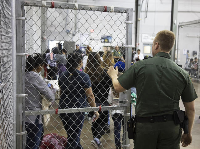 A U.S. Border Patrol agent watches as people taken into custody related to cases of illegal U.S. entry stand in line at a facility in McAllen, Texas, Monday. (Photo: U.S. Customs and Border Protection's Rio Grande Valley Sector via AP)