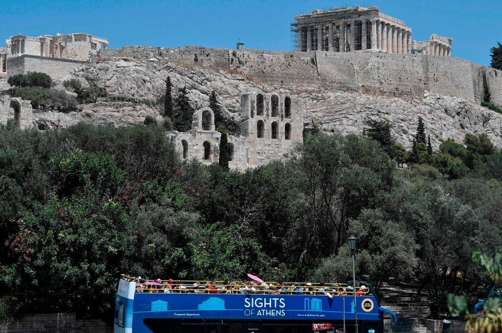 A tourist bus drives near the empty Acropolis archaeological site in Athens on July 4, 2019. The Acropolis closed for the hottest midday for 4 hours due to the heat wave in Athens. (Photo by LOUISA GOULIAMAKI / AFP/ Getty Images)