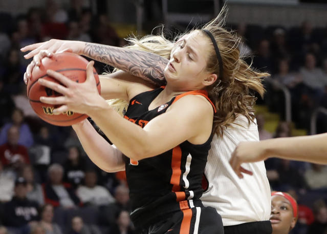 Oregon State guard Mikayla Pivec (0) battles for the ball with Louisville forward Sam Fuehring during the first half of a regional semifinal game in the NCAA women's college basketball tournament, Friday, March 29, 2019, in Albany, N.Y. (AP Photo/Kathy Willens)