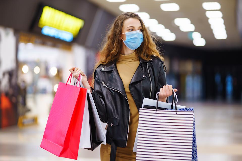 Young woman in protective medical mask with shopping bags using her phone. Purchases, black friday, discounts, sale concept. Online shopping concept.