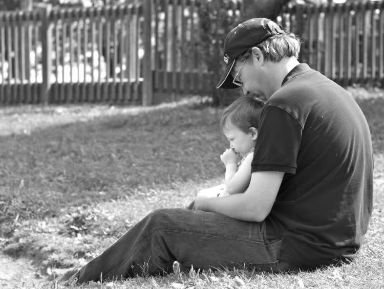 David holding his daughter, sitting in the grass