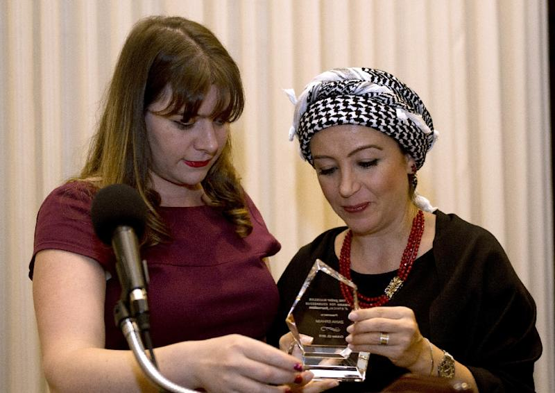 Syrian journalist Zaina Erhaim (R) receives the 2015 Peter Mackler award from Camille Mackler at the National Press Club in Washington, DC on October 22, 2015 (AFP Photo/Andrew Caballero-Reynolds)