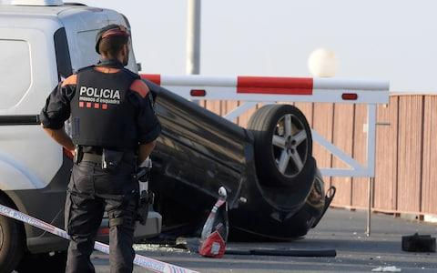 A policeman stands by a car involved in a terrorist attack in Cambrils,  - Credit: LLUIS GENE/AFP