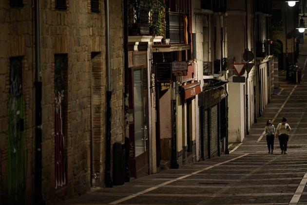 Residents wearing face masks as they walk along an empty Javier street, in Pamplona, northern Spain (AP Photo/Alvaro Barrientos)