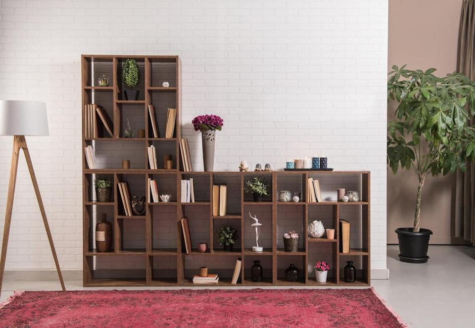 To instantly level-up your shelving style, try adjusting the space between shelves. So, rather than a perfectly symmetrical unit, you'll have shelves of various heights—some short, some tall, some wide, some in the middle. On most modern shelving units, you can do this by simply moving the holding pins up or down a few notches. From there, intersperse rows of decorative items and rows of books and, <em>voila</em>, you'll have a new focal point in your living room.