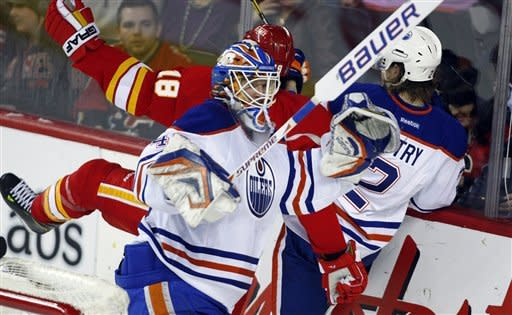 Edmonton Oilers goalie Devan Dubnyk, left, checks Calgary Flames' Matt Stajan, center, into teammate Jeff Petry during the first period of an NHL hockey game in Calgary, Alberta, Saturday, Jan. 26, 2013. (AP Photo/The Canadian Press, Jeff McIntosh)