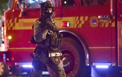 An armed police officer at the scene of the shooting in Toronto - Credit: Canadian Press/REX/Shutterstock