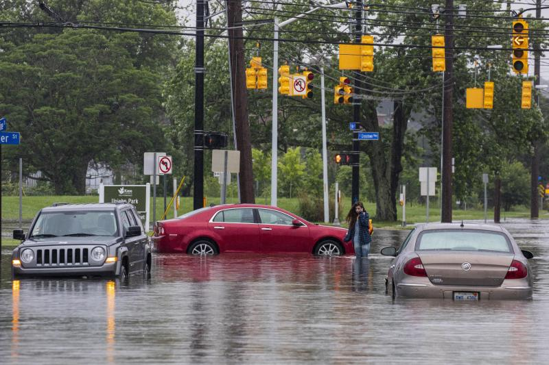 A woman walks back to her car after it was stranded in flood waters near the intersection of East Vine Street and East Crosstown Parkway in Kalamazoo, Mich., Thursday, June 20, 2019. (Photo: Joel Bissell/Kalamazoo Gazette via AP)