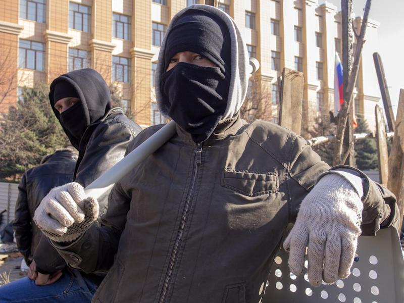 Pro-Russian activists in face masks stand near a barricade in front of an entrance of the Ukrainian regional office of the Security Service in Luhansk, 30 kilometers (20 miles) west of the Russian border, in Ukraine, Tuesday, April 8, 2014. A crowd of pro-Russian activists stormed the building on Sunday, April 6, 2014. Local media reported that demonstrators pelted the building with eggs, and then stones, a smoke grenade and finally a firebomb. The flames were reportedly quickly extinguished. (AP Photo/Igor Golovniov)