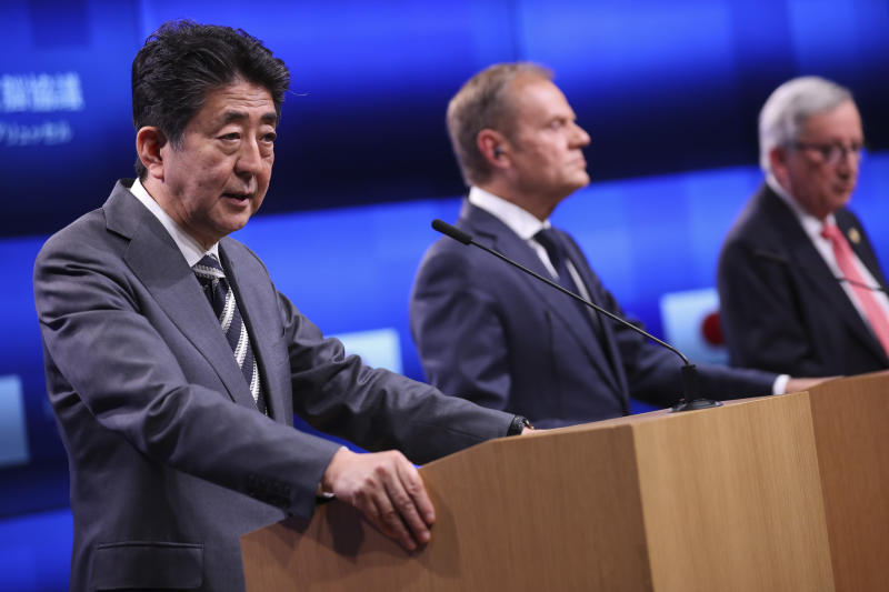 Japan's Prime Minister Shinzo Abe, left, talks to journalists during a joint news conference with European Commission President Jean-Claude Juncker, right, and European Council President Donald Tusk following their meeting during an EU-Japan summit at the European Council headquarters in Brussels, Thursday, April 25, 2019. Japanese Prime Minister Shinzo Abe and top EU officials discussed trade, bilateral ties and North Korea. (AP Photo/Francisco Seco)