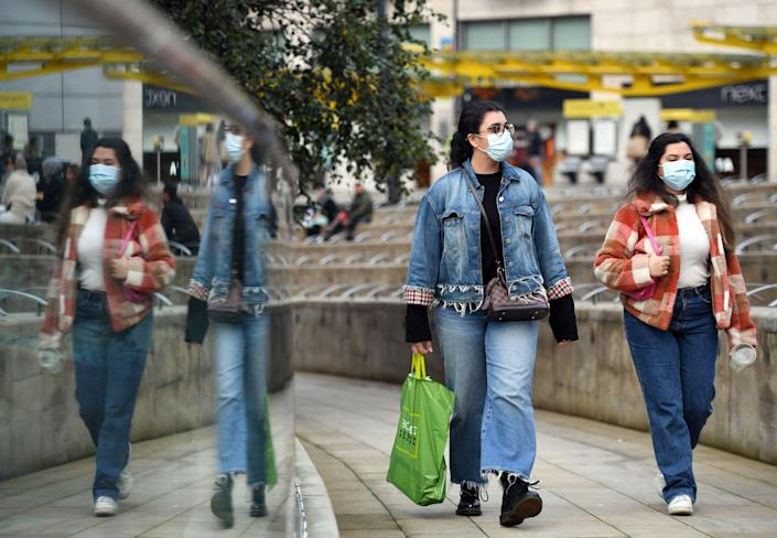 "People wear PPE masks and face coverings as they walk through the city centre in Manchester, north west England on October 8, 2020. - Pubs and restaurants in coronavirus hotspots look set to face fresh restrictions after Downing Street said new data suggests there is ""significant"" transmission taking place in hospitality settings. A ""range of measures"" is being looked at, with a particular focus on northern England, where it says infection rates are rising fastest. (Photo by Oli SCARFF / AFP) (Photo by OLI SCARFF/AFP via Getty Images)"