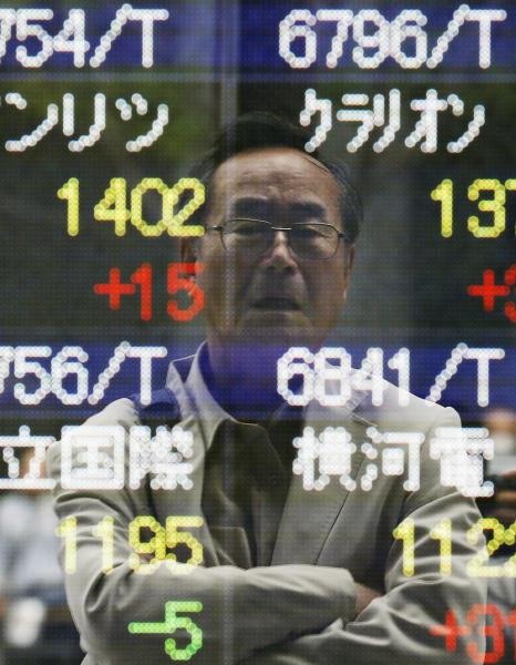 A man is reflected on the electronic board of a securities firm in Tokyo, Monday, May 13, 2013. Japan's stock market jumped Monday after global finance leaders gave a seal of approval to the country's stimulus program and refrained from criticizing its weakening effect on the yen. Stocks were mixed elsewhere in Asia. (AP Photo/Koji Sasahara)
