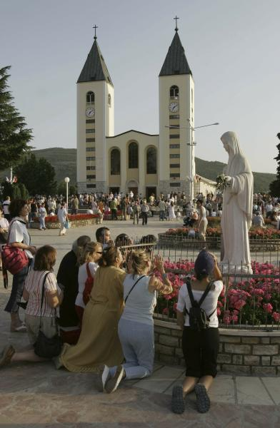 FILE - In this Saturday, June 24, 2006 file photo, pilgrims pray around a statue of the Virgin Mary during afternoon prayer service in front of the St James' Church at Medjugorje, Bosnia and Herzegovina, some 120 kilometers (75 miles) south of the Bosnian capital of Sarajevo. Pope Francis says pilgrimages can be organized to a Bosnian shrine where the Virgin Mary is reported to have appeared, but the Vatican is stressing that no decision has yet been taken on whether the apparitions in Medjugorje are authentic (AP Photo/Amel Emric, File)