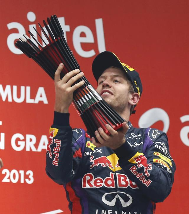 Red Bull Formula One driver Sebastian Vettel of Germany raises his trophy on the podium after winning the Indian F1 Grand Prix at the Buddh International Circuit in Greater Noida, on the outskirts of New Delhi, October 27, 2013. Vettel became Formula One's youngest four-times world champion on Sunday after winning the Indian Grand Prix for Red Bull. Red Bull also took the constructors' championship for the fourth year in a row. The victory from pole position was the 26-year-old's sixth in a row and completed a hat-trick of wins in India where no other driver has ever won since the race made its debut in 2011. REUTERS/Ahmad Masood (INDIA - Tags: SPORT MOTORSPORT F1 TPX IMAGES OF THE DAY)