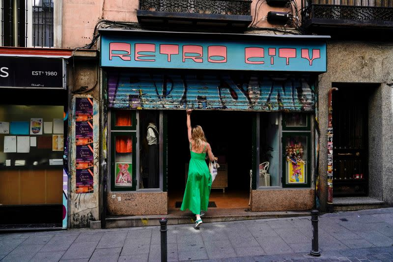 FILE PHOTO: A woman opens a shop at a commercial district in Madrid