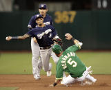 Milwaukee Brewers' Orlando Arcia (3) throws over Oakland Athletics' Chris Herrmann, right, to complete a double play on Chad Pinder during the fourth inning of a baseball game Tuesday, July 30, 2019, in Oakland, Calif. (AP Photo/Ben Margot)