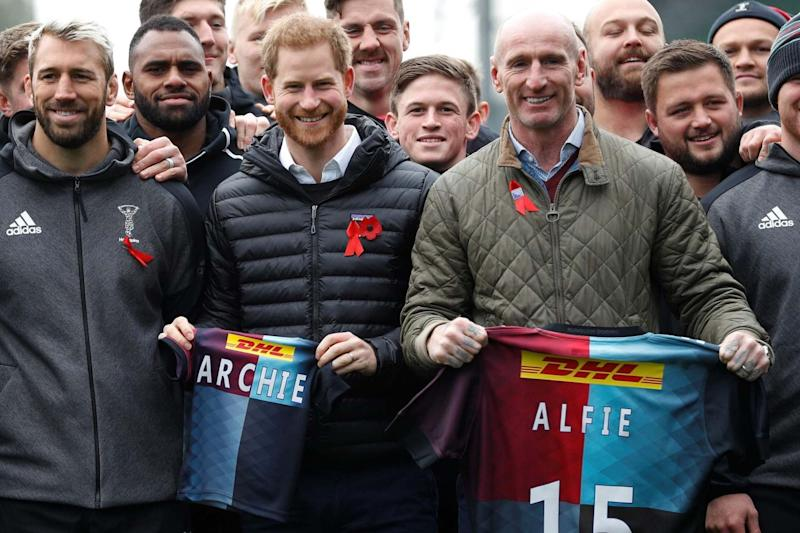 Prince Harry, Duke of Sussex (C) and former Welsh rugby player Gareth Thomas (CR) hold shirts gifted by Harlequins rugby club (POOL/AFP via Getty Images)